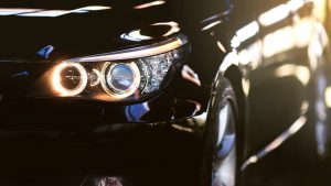 closeup of a car headlight and black body work